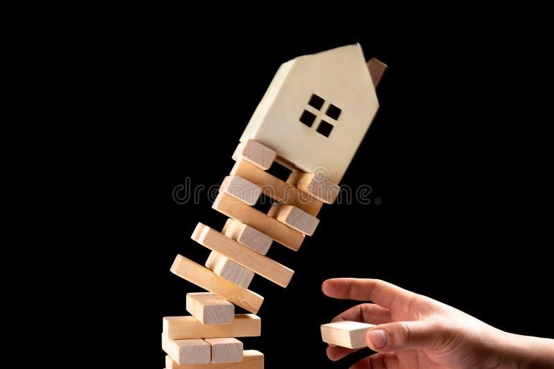 Haus, das unten vom instabilen niedrigen Konzept von Immobilien invesetment fällt stockfotografie