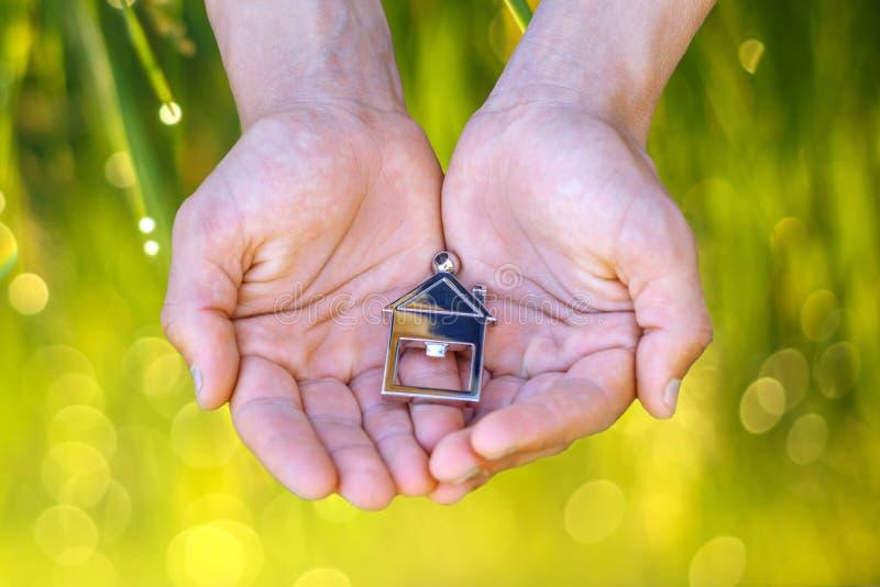 Haus in den Händen des Konzeptes des Kaufens von Immobilien natürlichen Hintergrund lizenzfreies stockfoto