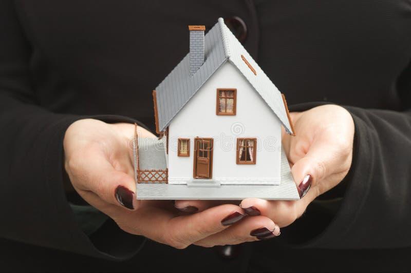 Haus in den weiblichen Händen lizenzfreies stockbild