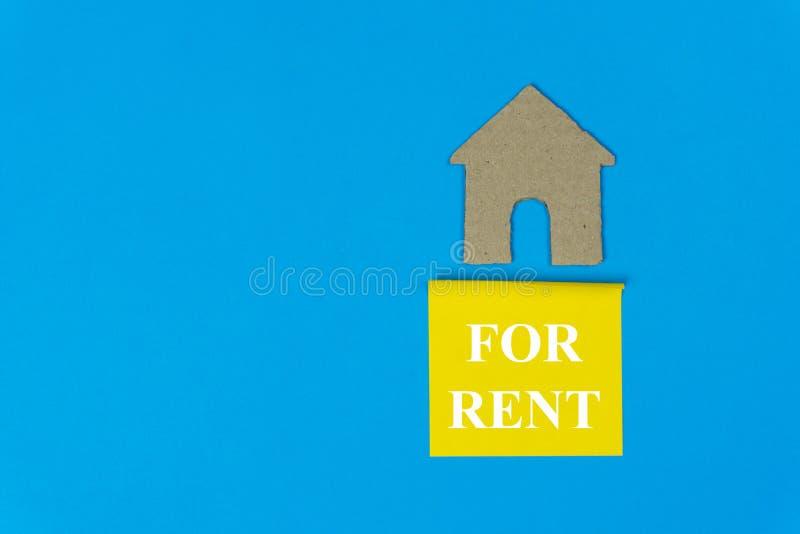 Haus f?r Miete Eigentumsmietkonzept Immobilienverkaufszeichen unter einem kleinen Haus gemacht durch Papierschnitt auf blauem Hin stockfoto