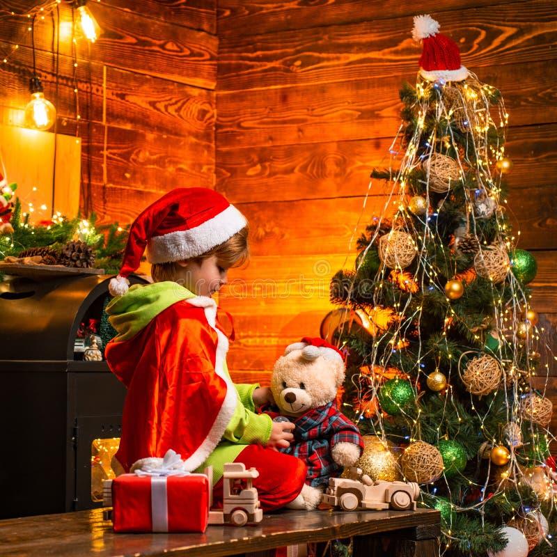 Haus gef?llt mit Freude und Liebe Nettes kleines Kinderjungenspiel nahe Weihnachtsbaum Geschenke und ?berraschungen Frohe Weihnac lizenzfreie stockfotos
