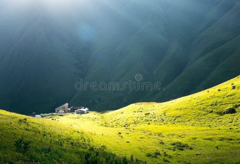 Haus im Sonnenlicht, in einem grünen Gebirgstal stockfotos