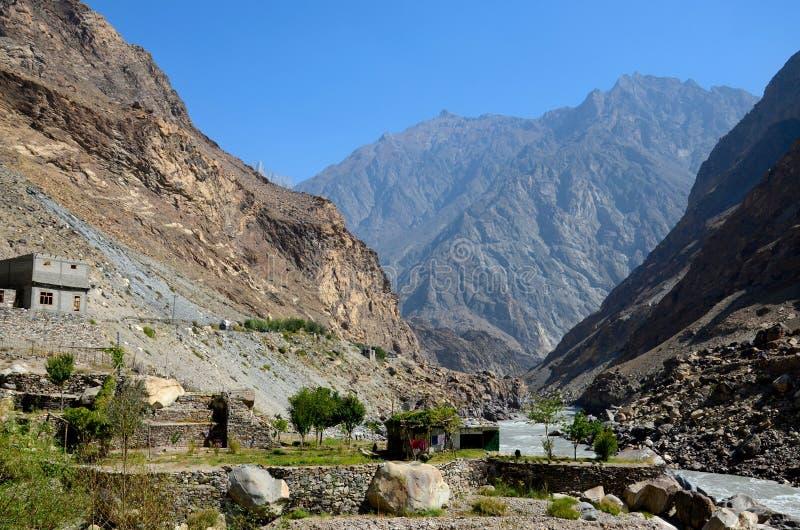 Haus im Tal durch Flussufer und hängende Wäscherei unter Bergen Skardu Pakistan stockfoto