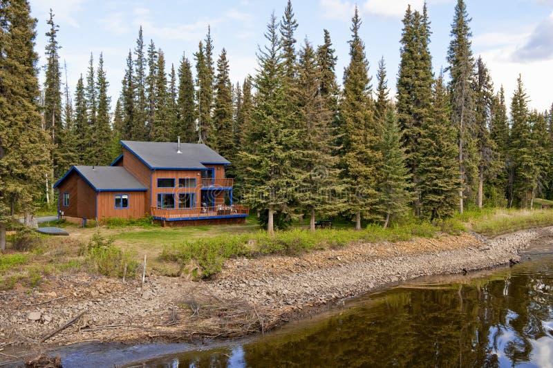 Haus im Wald durch Fluss lizenzfreies stockfoto