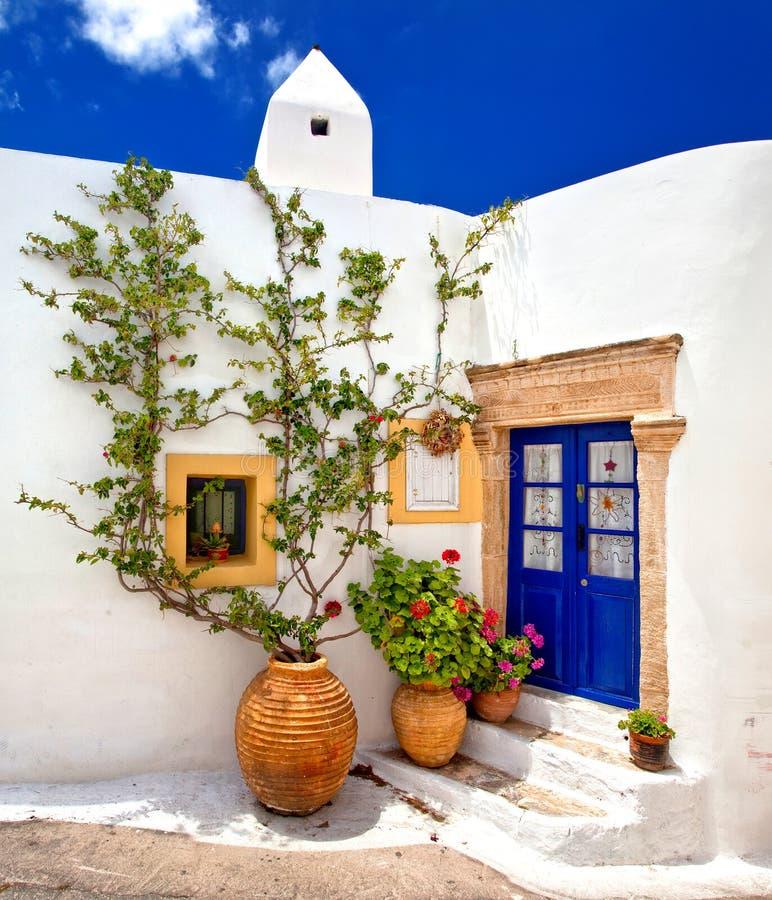 Haus mit blauer Tür und Blumen stockfotos