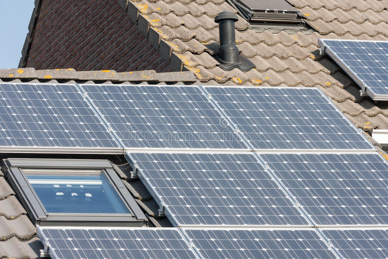 Haus mit Dach und Sonnenkollektoren stockbild