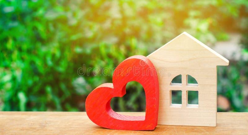 Haus mit einem roten hölzernen Herzen Haus von Liebhabern Erschwingliche Wohnung für junge Familien Valentinsgruß ` s Tageshaus lizenzfreies stockbild