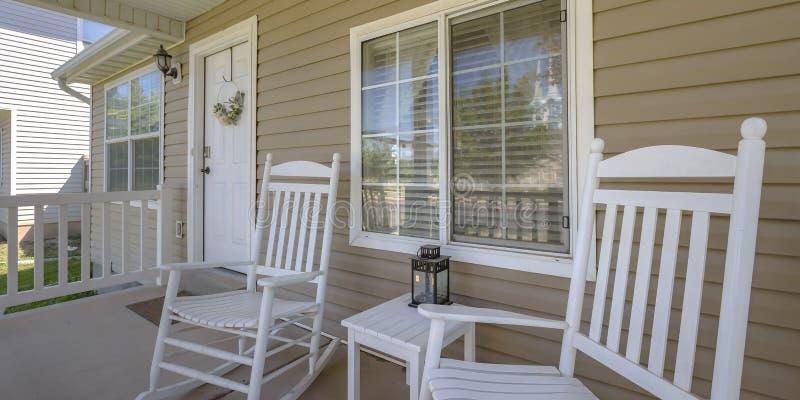 Haus mit Schaukelstühlen und Tabelle auf Eingangsterrasse lizenzfreies stockfoto