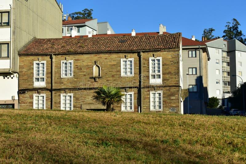 Haus mit Steinziegelsteinen, weißen hölzernen Fenstern, Dachplatten und Palme Allgemeiner Park, sonniger Tag, blauer Himmel lizenzfreies stockbild