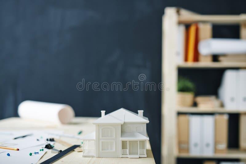Haus-Modell auf Schreibtisch im Büro lizenzfreies stockfoto