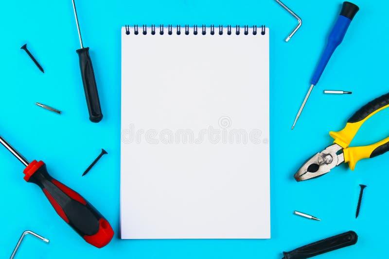 Haus, Haus-Reparatur, Neu streichen, Konzept erneuernd Ein Satz Reparaturwerkzeuge auf einem blauen Gitter: zwei Schraubenzieher  stockfotos