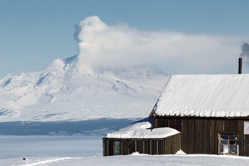 Haus Volcanologists auf Hintergrunderuptionsvulkan stockfotografie