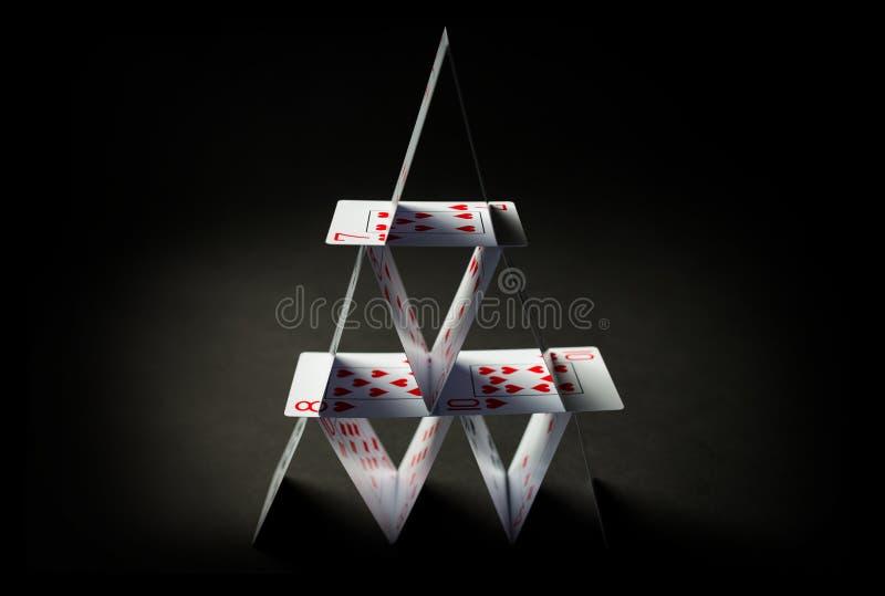 Haus von Spielkarten über schwarzem Hintergrund lizenzfreies stockbild