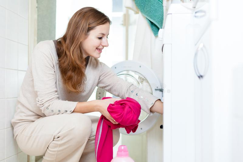Hausarbeit: junge Frau, die Wäscherei tut stockfotografie