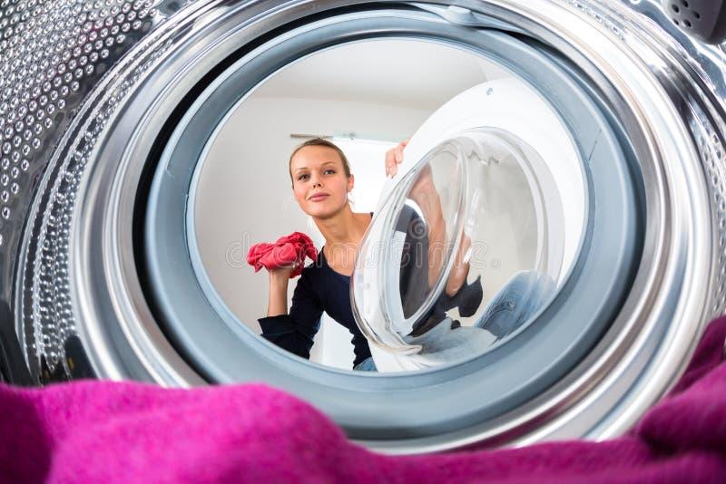 Hausarbeit: junge Frau, die Wäscherei tut lizenzfreies stockbild