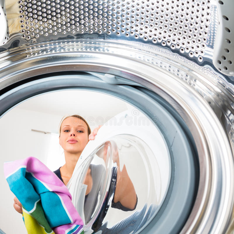Hausarbeit: junge Frau, die Wäscherei tut stockbild