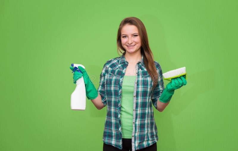 Hausarbeit- und Haushaltungskonzept Reinigungsfrau, die das Reinigungsspray-Flaschenschießen glücklich und das Lächeln zeigt Rein lizenzfreie stockfotos