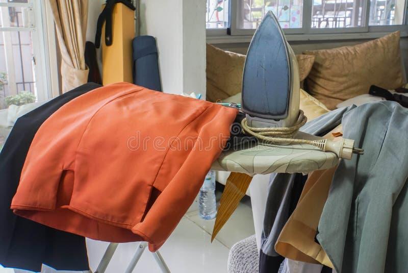 Hausarbeitkonzeptrock und Mannkleidung, damit das Bügeln arbeitet stockfotos