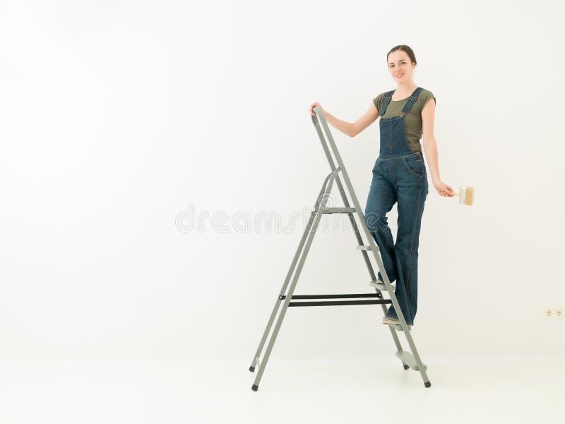 Hausarbeitmädchen auf einer Leiter stockfoto