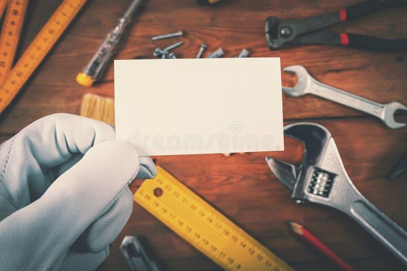Hausbau- und -reparaturdienstleistungen - Arbeitskraft, die leere Visitenkarte über Arbeitswerkzeugen hält lizenzfreie stockfotos