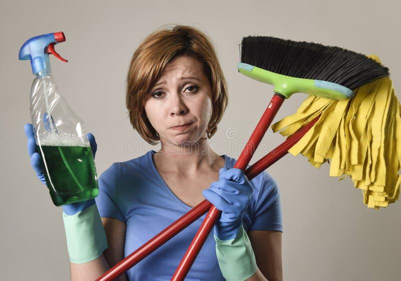 Hausfrau in den waschenden Gummihandschuhen, die Reinigungssprühflasche tragen, kehren und wischen lizenzfreie stockbilder