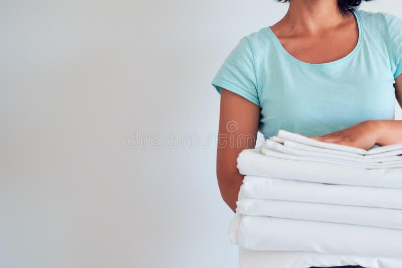 Hausfrau, die einen Stapel gewaschene Bettwäsche hält waschende Kleidung und Leinen, Bleiche von weißen Sachen lizenzfreie stockfotos