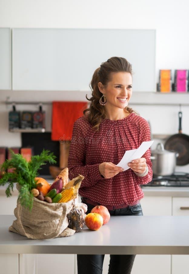 Hausfrau, die Einkaufkontrollen hält stockbilder