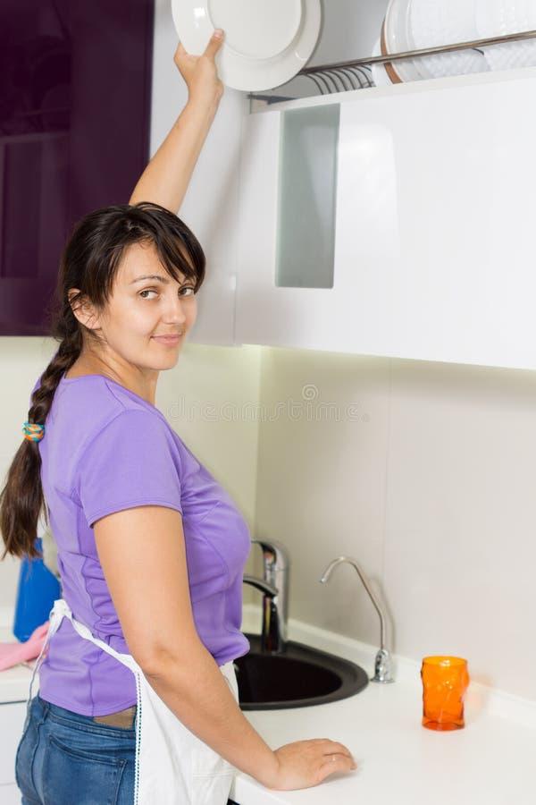 Hausfrau, die für eine Platte in der Küche erreicht stockfotos