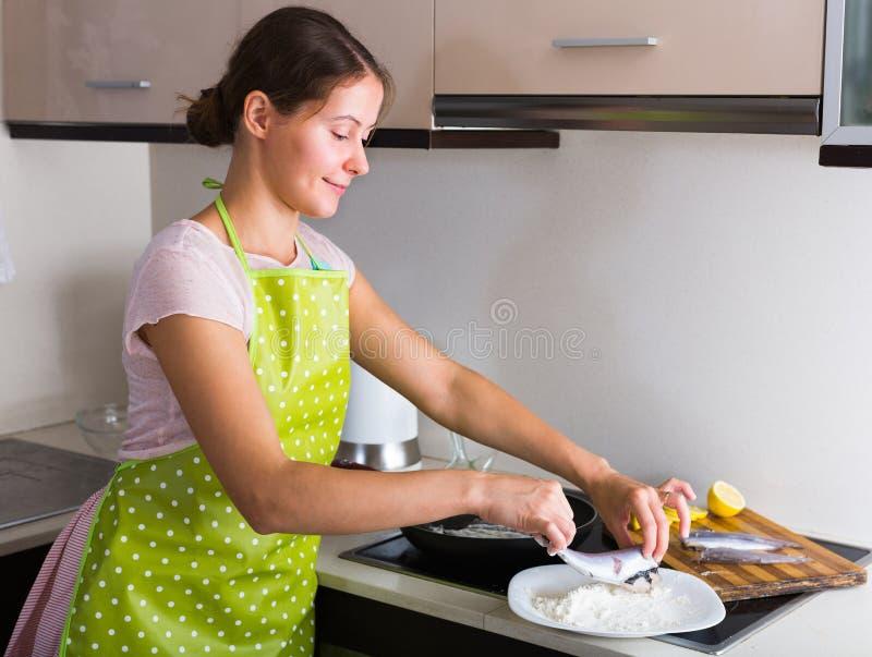 Hausfrau, die Fische an der Küche brät stockbild