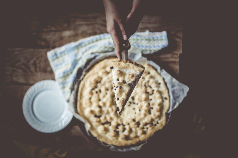 Hausfrau, die gerade gebackenen K?sekuchen schneidet Hand, die frisch gebackenen Kuchen mit H?ttenk?se schneidet lizenzfreie stockfotos