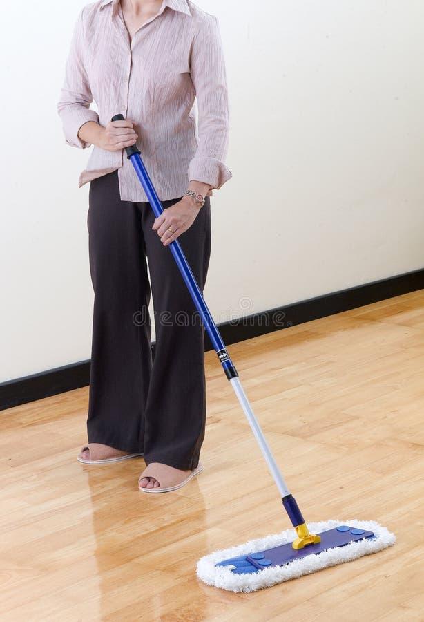 Hausfrau, die hölzernen Fußboden durch Mopp säubert stockfoto