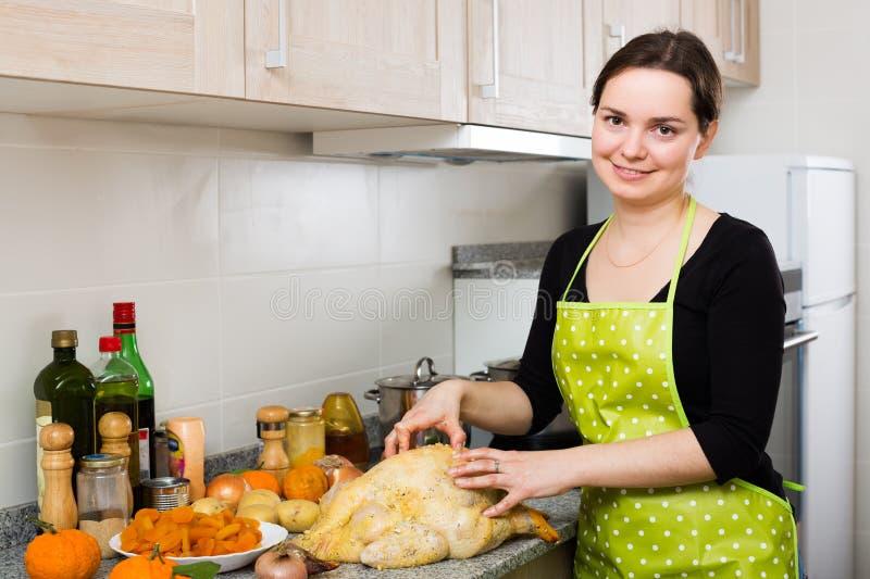 Hausfrau, die mit Kapaun aufwirft lizenzfreie stockfotos