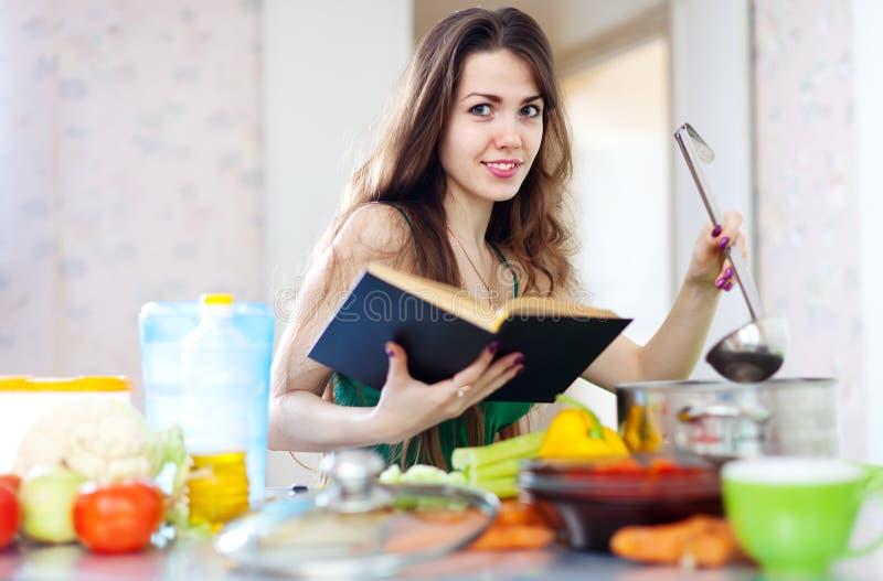 Hausfrau, die mit Schöpflöffel und Kochbuch kocht lizenzfreies stockfoto