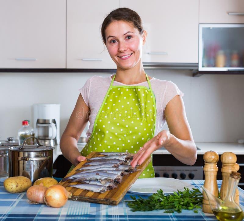 Hausfrau, die neues Rezept von sprattus in der Küche versucht lizenzfreie stockfotos