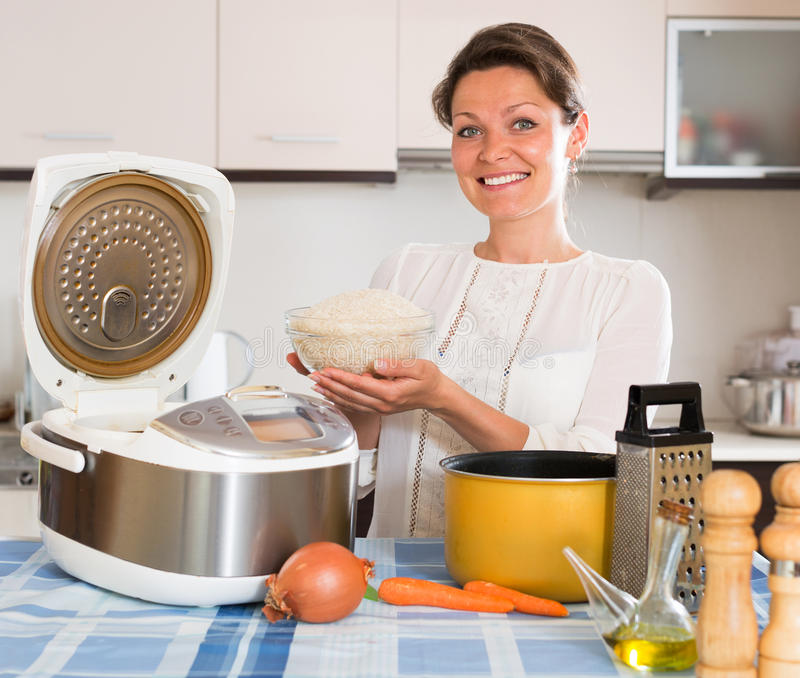 Hausfrau, die Reis mit multicooker kocht stockfoto