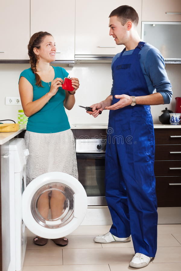 Hausfrau, die Schlosser für Arbeit zahlt lizenzfreies stockfoto