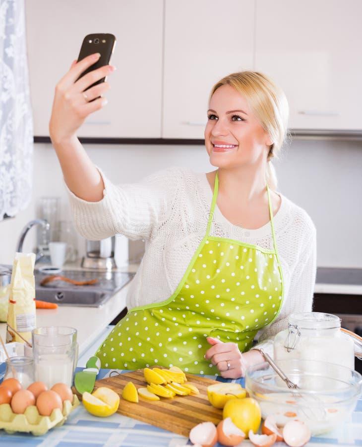 Hausfrau, die selfie an der Küche tut lizenzfreies stockfoto