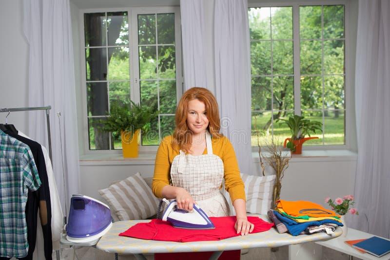 Hausfrau, die Wäscherei und das Bügeln tut lizenzfreie stockfotos
