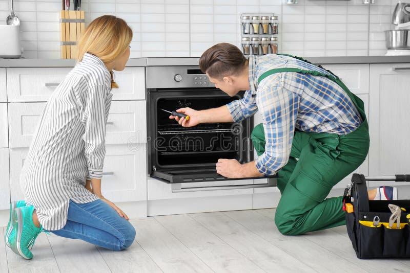 Hausfrau mit Arbeitskraft nahe Ofen stockbild