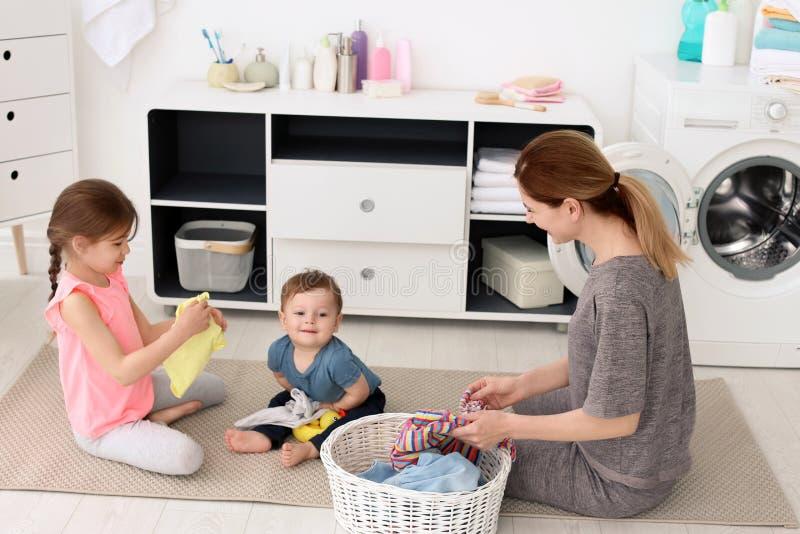 Hausfrau mit den Kindern, die frisch gewaschene Kleidung falten lizenzfreie stockfotos