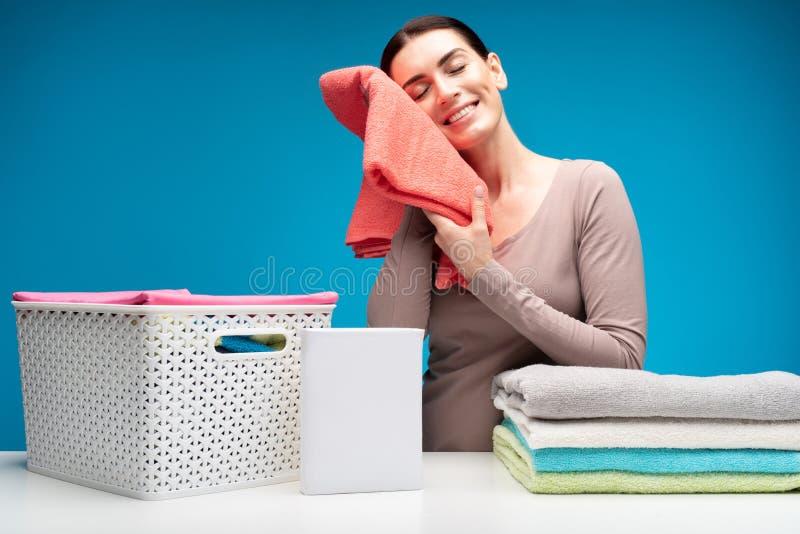 Hausfrau mit sauberem Leinen am Wäschereitisch lizenzfreie stockbilder
