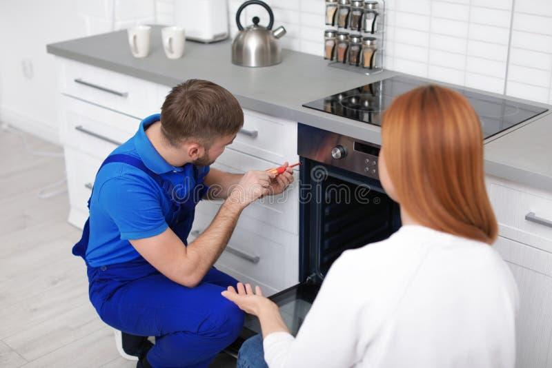 Hausfrau mit Schlosser nahe modernem Ofen lizenzfreie stockfotos