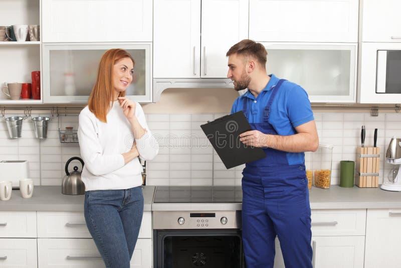 Hausfrau mit Schlosser nahe modernem Ofen stockfoto