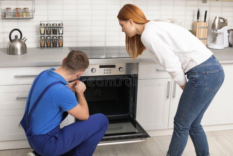 Hausfrau mit Schlosser nahe modernem Ofen stockbilder