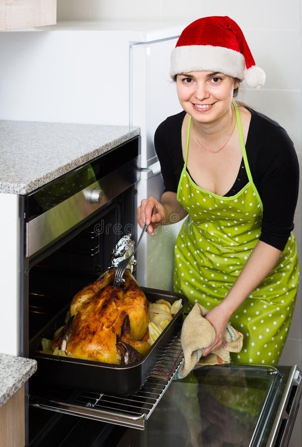 Hausfrau in Sankt-Hut, der festlichen Kapaun backt lizenzfreies stockbild