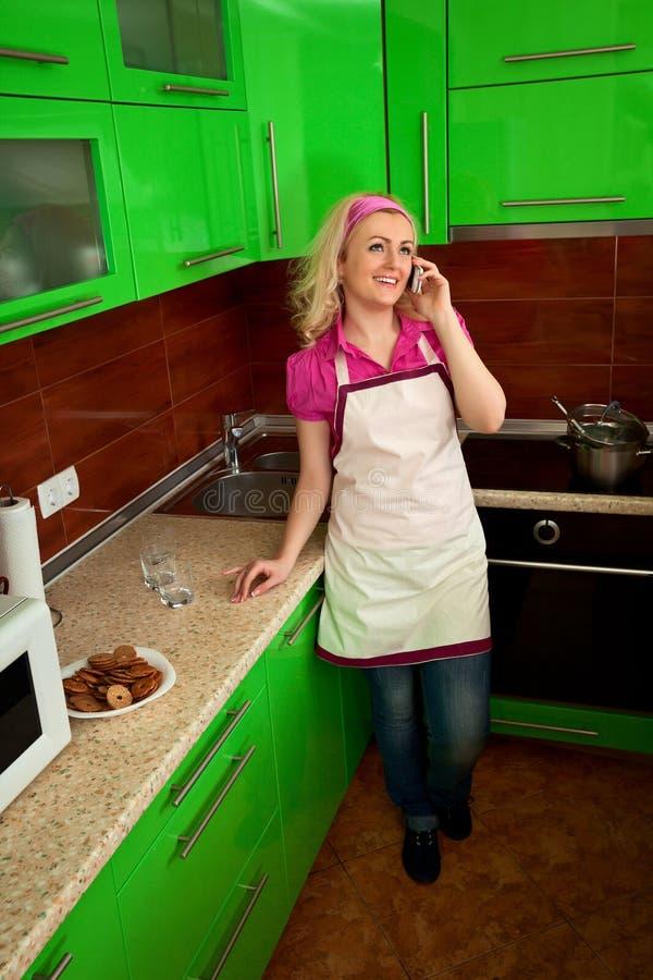 Hausfrau, spricht an einem Telefon in der Küche lizenzfreie stockfotos