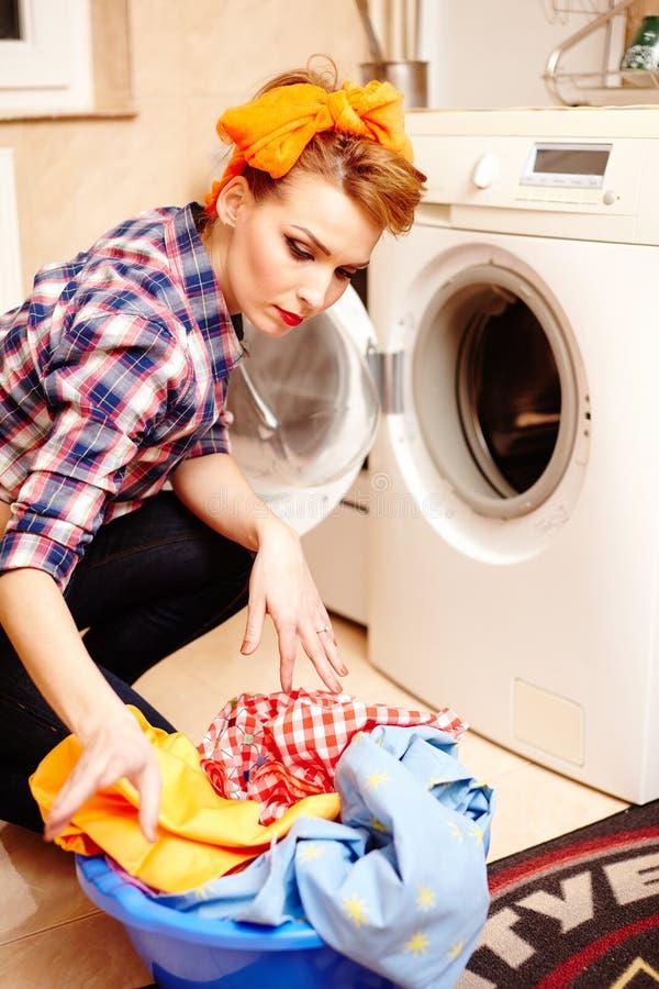 Hausfrau, welche die Wäscherei in die Waschmaschine setzt stockfotos