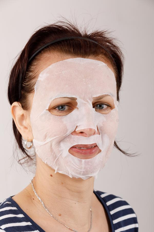 Hausfraufrau mit einer Blattmaske auf ihrem Gesicht stockfotos