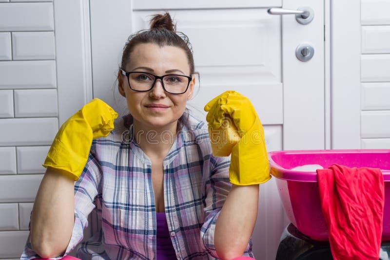 Hausfraufrau säubert in das Badezimmer Betrachtet die Kamera, geduckt nahe der Tür, nahe bei dem Becken, Lappen stockfotografie