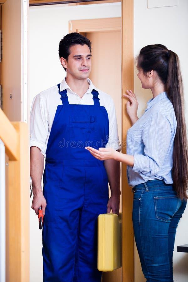 Hausfraugrußklempner am Hauseingang lizenzfreies stockfoto